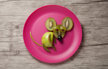 fruit plate: Mouse made of kiwi and apple on wooden background Stock Photo
