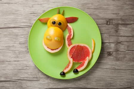 aliments droles: Giraffe made of juicy fruits on plate Banque d'images