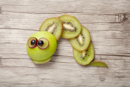 aliments droles: Caterpillar made of kiwi, apple and grape on desk