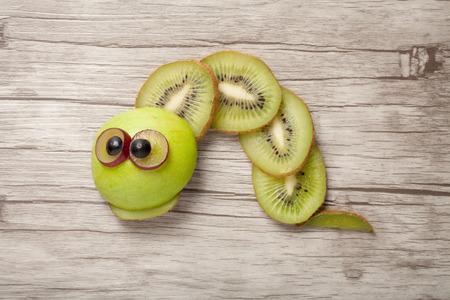 children caterpillar: Caterpillar made of kiwi, apple and grape on desk
