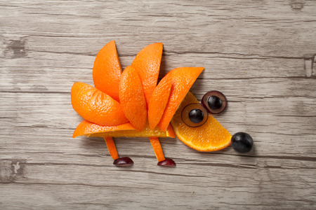 aliments droles: Hedgehog made of orange and grape on wooden desk