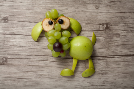 healthy meals: Dog made of apple, grape and banana on board Stock Photo