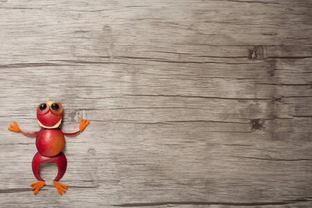 red frog: Red frog made of apple on wooden background