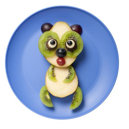 Amusing panda made of pear and kiwi on plate