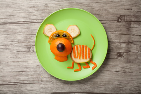 Amusing tiger made of orange on plate and board Stock Photo