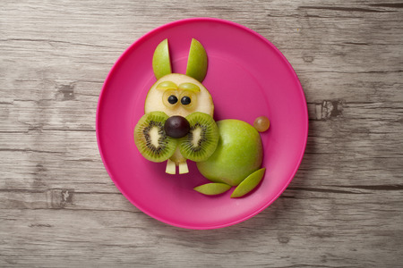 aliments droles: Rabbit made of fruits on plate and board