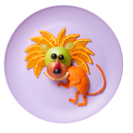 caricature cat: Sneaky lion made of orange and apple on plate Stock Photo