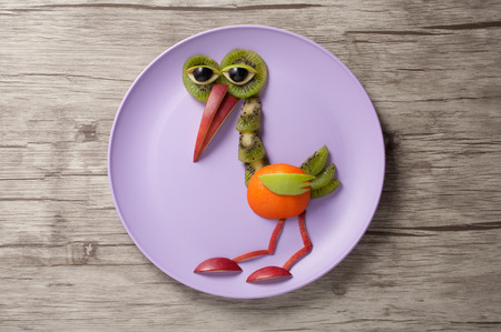 Heron made of fruits on plate and desk Stock Photo
