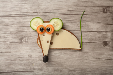 Mouse made of bread and cheese on wooden background Stock Photo