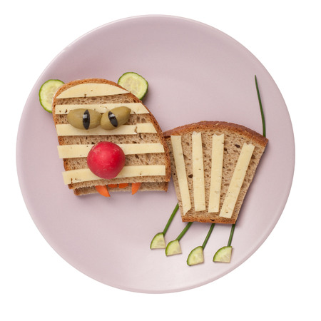 Sad tiger made of cheese and bread on plate