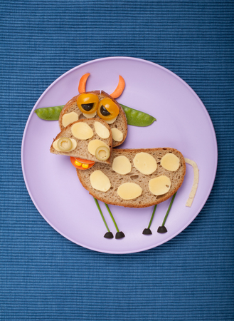 cow pea: Sad cow made of bread and vegetables on plate and fabric Stock Photo