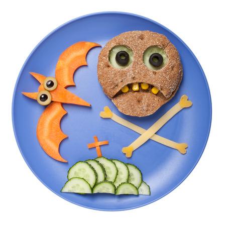 calavera caricatura: Halloween del cráneo y bate hechas de pan y verduras en un plato Foto de archivo