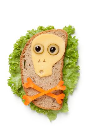 calavera caricatura: Calavera de Halloween hecha de pan y verduras en el fondo blanco