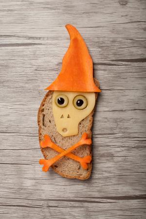 calavera caricatura: Halloween del cráneo hecha de pan y hortalizas en la plancha