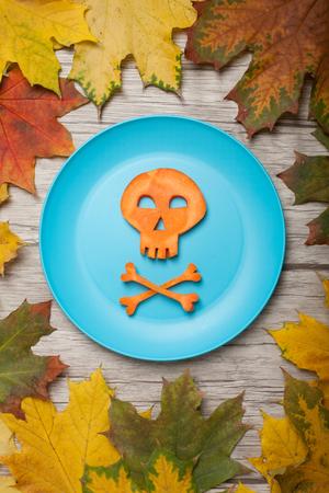 calavera caricatura: Cráneo de Halloween de zanahoria en placa y fondo de otoño