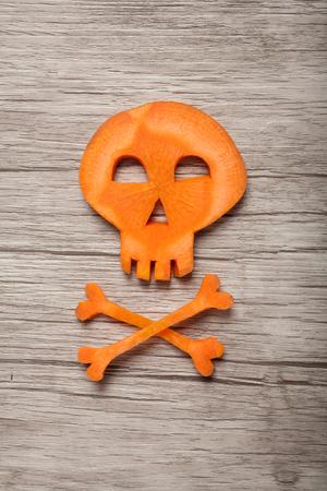 calavera caricatura: Cráneo de Halloween hecho de zanahoria en el fondo de madera