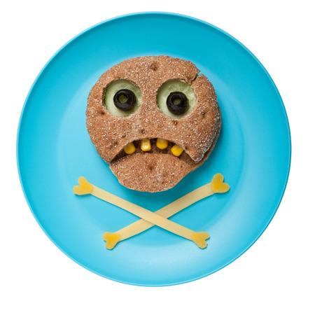 calavera caricatura: Halloween del cráneo hecha de pan y verduras en un plato