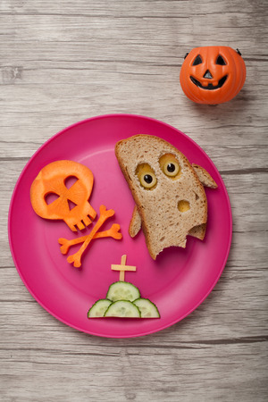 wraith: Halloween ghost and skull made of bread and carrot on board
