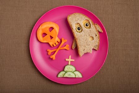 calavera caricatura: fantasma de Halloween y el cráneo hechas de pan y zanahoria en la tela