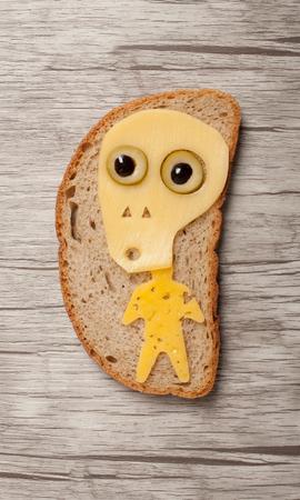 calavera caricatura: Cráneo de Halloween hecha de queso en el pan y escritorio
