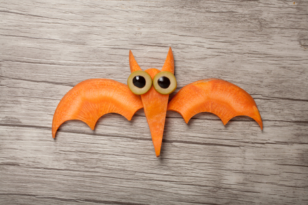 Halloween bat made of carrot on board