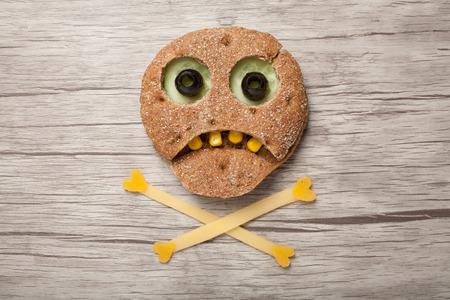 calavera caricatura: Halloween del cráneo hecha de pan y verduras en el fondo de madera Foto de archivo