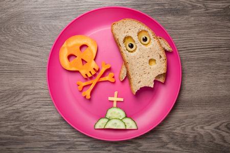 calavera caricatura: Fantasma de Halloween y cráneo hecho de pan y zanahoria en placa y escritorio