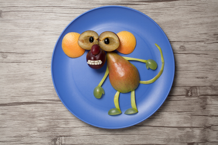Funny fruit ape on plate and wooden background