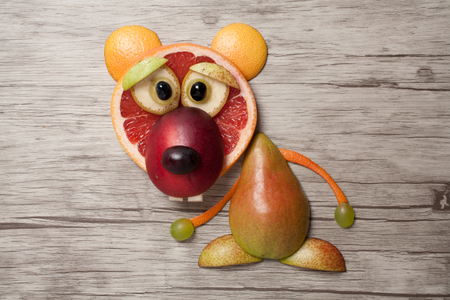 Funny fruit bear made on wooden background
