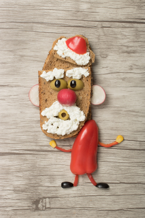 Dancing Santa made as sandwich on wooden background