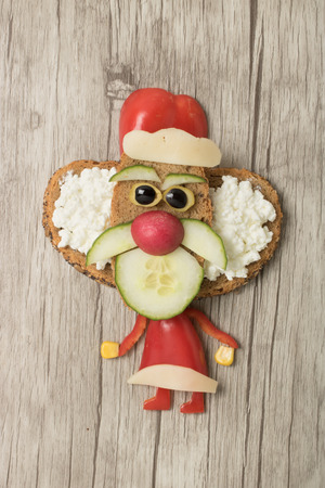Santa made with vegetables on wooden background