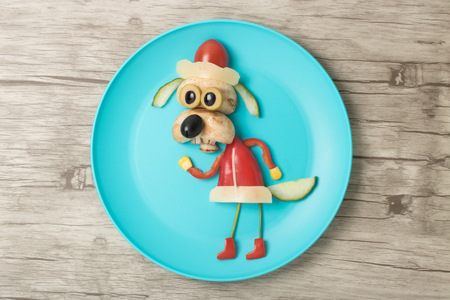 Santa dog made with vegetables on blue plate