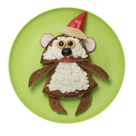 Bear composed of bread and cheese with pepper Santa hat on green plate Stock Photo