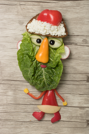 Santa made from salad and pepper on wooden background