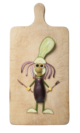 Amusing cook compiled from eggplant and cucumber on cutting board