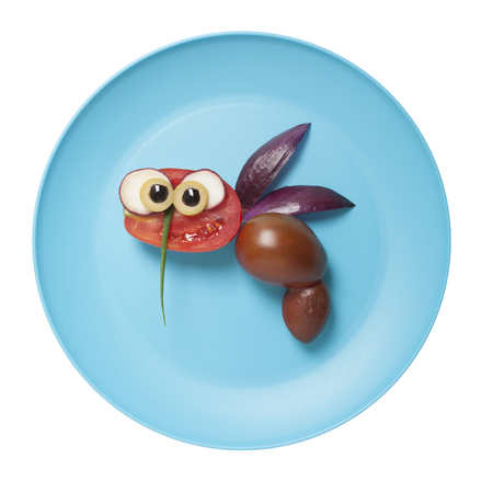 Bee compiled from tomatoes and onion on blue plate