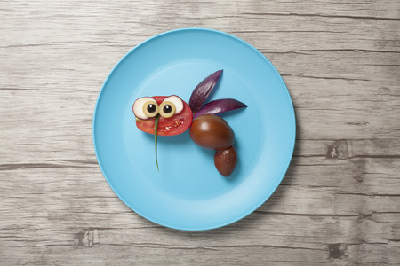 Funny bee made with vegetables on plate and desk