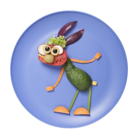Funny rabbit compiled from vegetables on blue plate Stok Fotoğraf