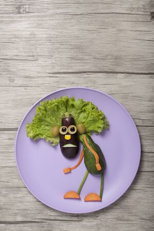 Amazed male compiled from vegetables on plate