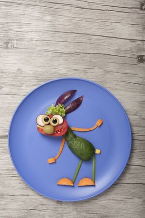 Vegetable rabbit made on blue plate and wooden board Stok Fotoğraf