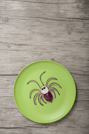 Funny vegetable spider made on green plate and wooden background