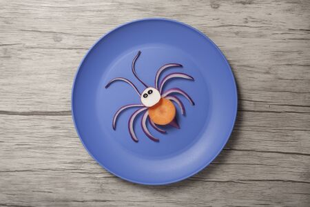Spider made with onion and carrot on plate and desk