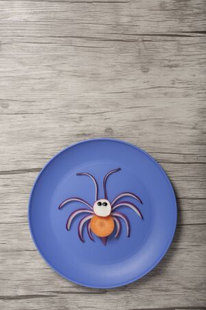 Idea of making a spider from onion and carrot on blue plate
