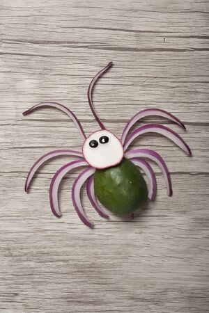 Spider made with cucumber, radish and onion on wooden background Stok Fotoğraf