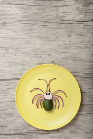 Spider made of vegetables on yellow plate and board