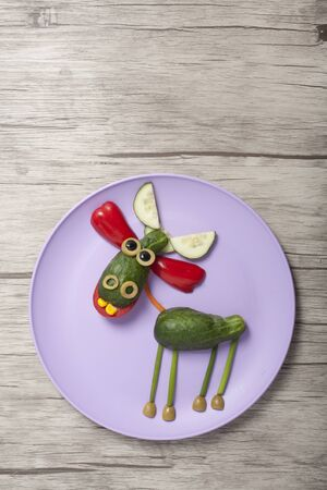 Deer created from cucumber on plate and desk