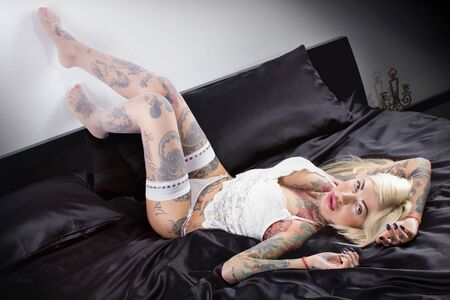 similarity: the beautiful woman with tattoos in underwear on a bed