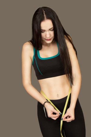 measures: the beautiful young woman on a gray background measures in black sportswear to herself waist volume