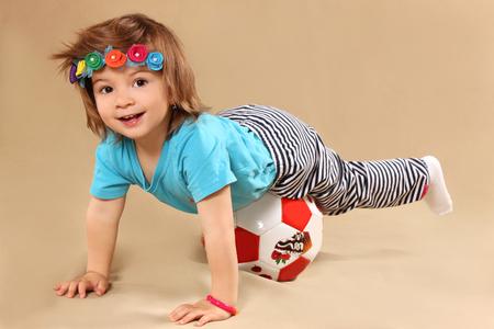 futbol infantil: the little girl lies from above on a ball