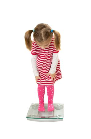 weight control: Little funny girl stand on scales. white background